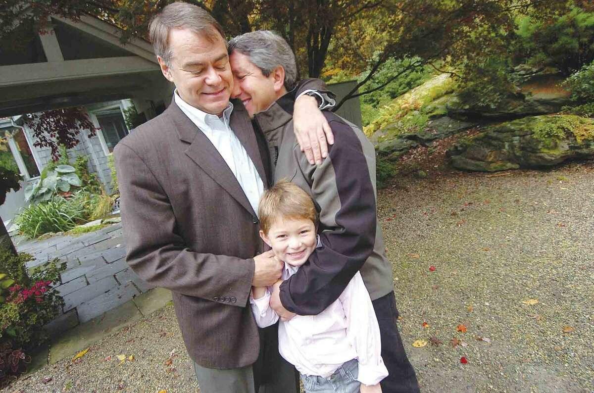Hour File Photo/Alex von Kleydorff. l-r Stephen Davis and Jeffrey Busch get 6yr old Elijah ready to head off to school.