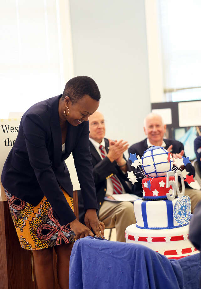 Guest of Honor, Ms. Carol Wainaina, cuts a celebratory cake on behalf the United Nations during Westport's 50th jUNe Day Celebration Ceremony at Saugatuck Elementary School Saturday morning. Hour Photo / Danielle Calloway