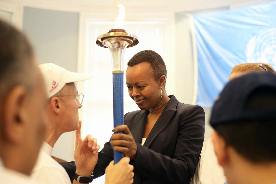Guest of Honor, Ms. Carol Wainaina, holds the Torch of Peace on behalf of the United Nations during Westport's 50th jUNe Day Celebration Ceremony at Saugatuck Elementary School Saturday morning. Hour Photo / Danielle Calloway
