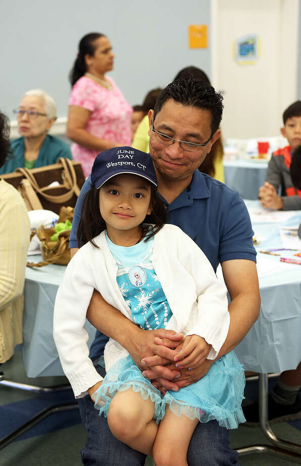 Joe Myat and his daughter Sophie, 8, sit together during Westport's 50th jUNe Day Celebration Ceremony at Saugatuck Elementary School Saturday morning. Hour Photo / Danielle Calloway