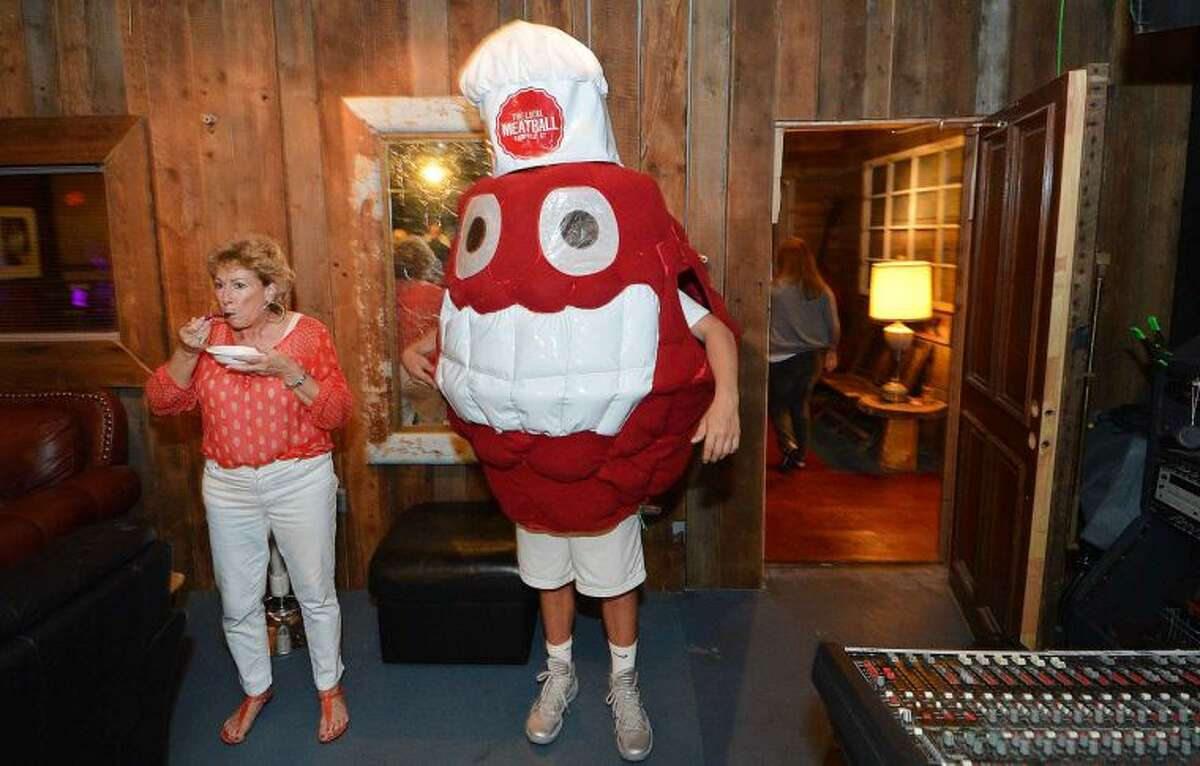 Hour Photo/Alex von Kleydorff Debbie Santos finds a quite spot to sample, next to the Local Meatball Co. Mascot during The Meatball Challenge of Fairfield County at The Factory Underground in Norwalk