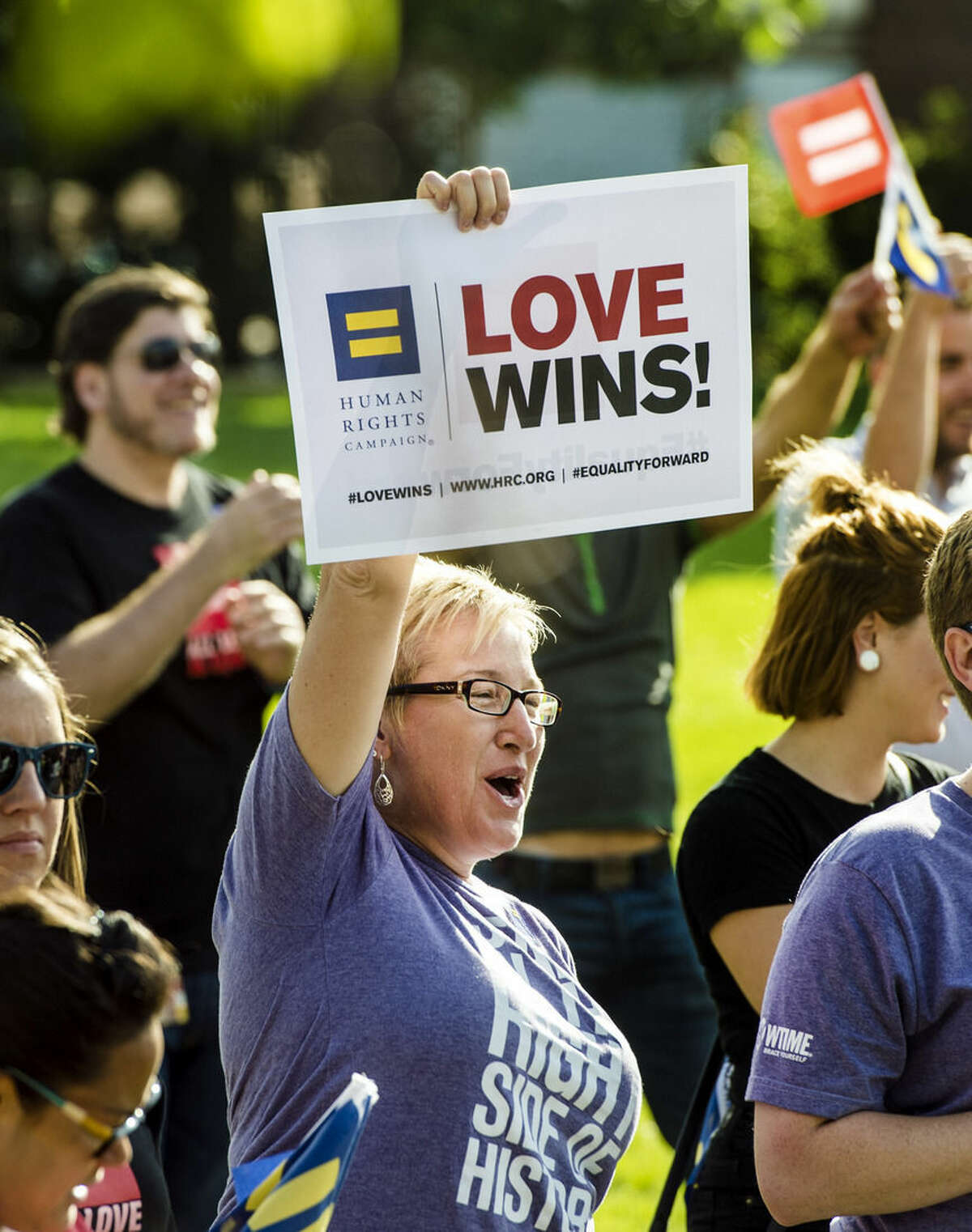 Tracy White, of Kansas City, Mo., celebrates after the Supreme Court declared that same-sex couples have a right to marry anywhere in the United States, at Ilus E. Davis Park in Kansas City, Mo., Friday, June 26, 2015(Allison Long/The Kansas City Star via AP)