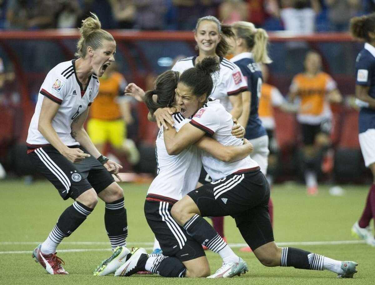 Germany's Celia Sasic, right, celebrates with teammates Simone Laudehr, left, and Dzsenifer Marozsan after scoring from the penalty spot against France during the second half of a FIFA Women's World Cup quarterfinal soccer game, Friday, June 26, 2015, in Montreal, Canada. (Graham Hughes/The Canadian Press via AP) MANDATORY CREDIT