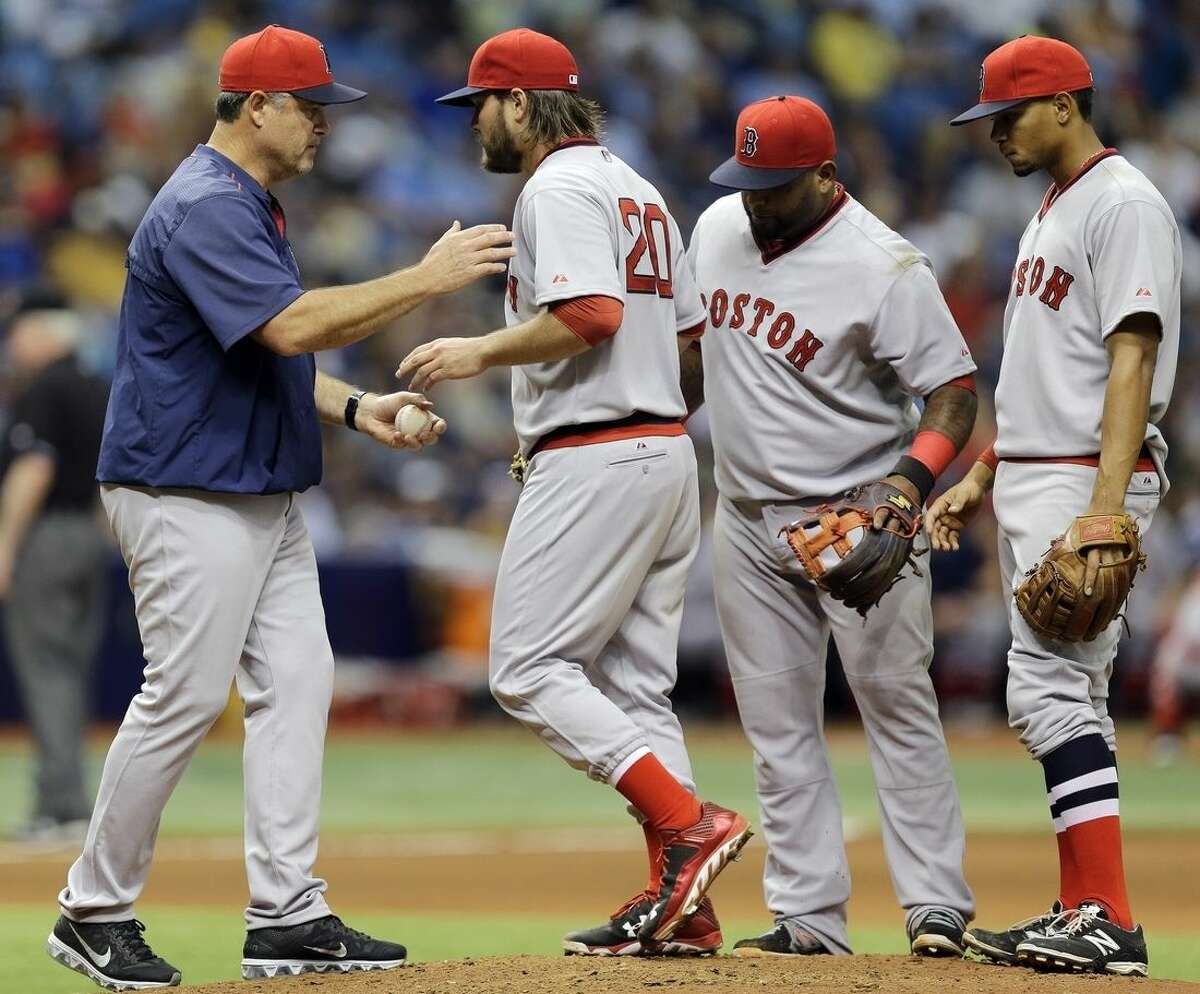 Boston Red Sox starting pitcher Wade Miley, second from left, hands the ball to manager John Farrell, left, after being taken out of a baseball game against the Tampa Bay Rays during the seventh inning Saturday, June 27, 2015, in St. Petersburg, Fla. Red Sox's Xander Bogaerts, right, and Pablo Sandoval, second from right, look on. (AP Photo/Chris O'Meara)