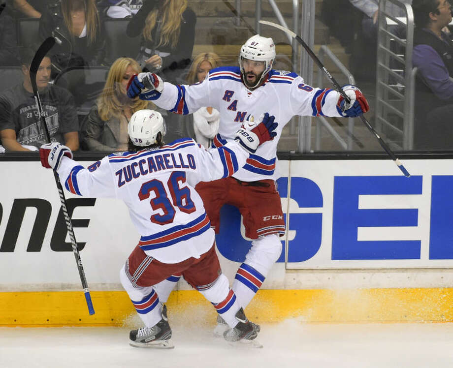 New York Rangers left wing Benoit Pouliot, right, celebrates his goal with right wing Mats Zuccarello, of Sweden, against the Los Angeles Kings during the first period in Game 1 of the NHL hockey Stanley Cup Finals, Wednesday, June 4, 2014, in Los Angeles. (AP Photo/Mark J. Terrill)