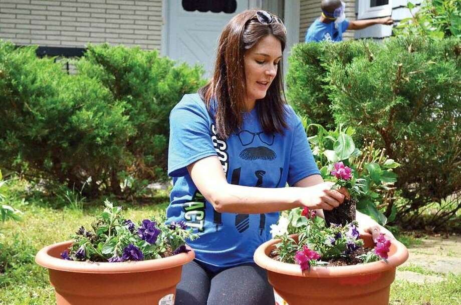 Hour photo / Liana Sonenclar Kristin Schwenk, a Deloitte employee, pots flowers Friday as part of the 15th anniversary of IMPACT Day.