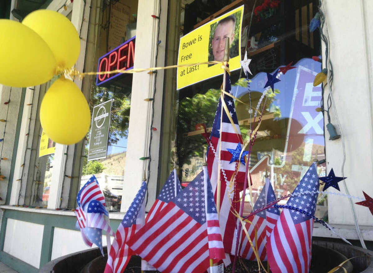 Flags and balloons marking the release from captivity of Sgt. Bowe Bergdahl adorn the sidewalk outside a shop in the soldier's hometown of Hailey, Idaho, Wednesday, June 4, 2014. The exchange for five Taliban detainees from Guantanamo and the still-murky circumstances of how Bergdahl came to be captured nearly five years ago have prompted a fierce debate in Washington and across the country. (AP Photo/Brian Skoloff)