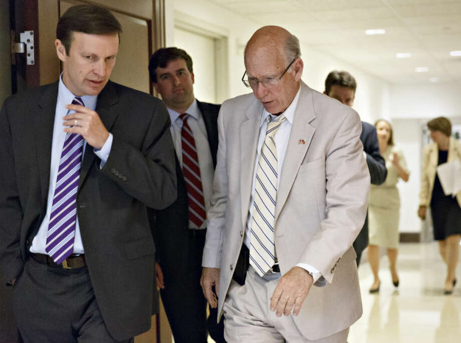 Sen. Chris Murphy, D-Conn., left, confers with Sen. Pat Roberts, R-Kan., as they join other senators for a closed-door briefing with intelligence officials about the Obama administration's decision to swap five members of the Taliban for captive Army Sgt. Bowe Bergdahl, at the Capitol in Washington, Wednesday, June 4, 2014. (AP Photo/J. Scott Applewhite)