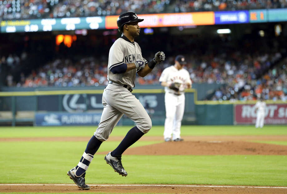 New York Yankees' Chris Young, left, runs the bases after hitting a two-run home run off Houston Astros starting pitcher Brett Oberholtzer, right, during the second inning of a baseball game Saturday, June 27, 2015, in Houston. (AP Photo/David J. Phillip)