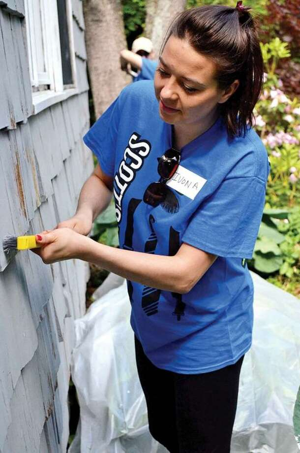 Hour photo / Liana Sonenclar Ivona Unger, a Deloitte employee, prepares shingles for paint Friday as part of the 15th anniversary of IMPACT Day.