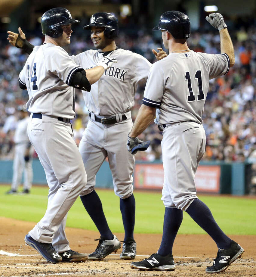 New York Yankees' Brian McCann (34) is congratulated by Brett Gardner (11) and Chris Young, center, after hitting a grand slam during the first inning of a baseball game against the Houston Astros Saturday, June 27, 2015, in Houston. All three and Alex Rodriguez scored on McCann's homer. (AP Photo/David J. Phillip)