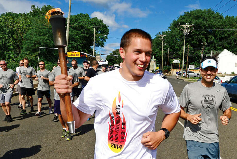Hour photo / Erik Trautmann Stamford police officers including Nick Jentz take part in the Law Enforcement Torch Run for Special Olympics Connecticut Friday. The torch will end up in New Haven where the 2014 Special Olympics Summer Games at Southern Connecticut State University are taking place.