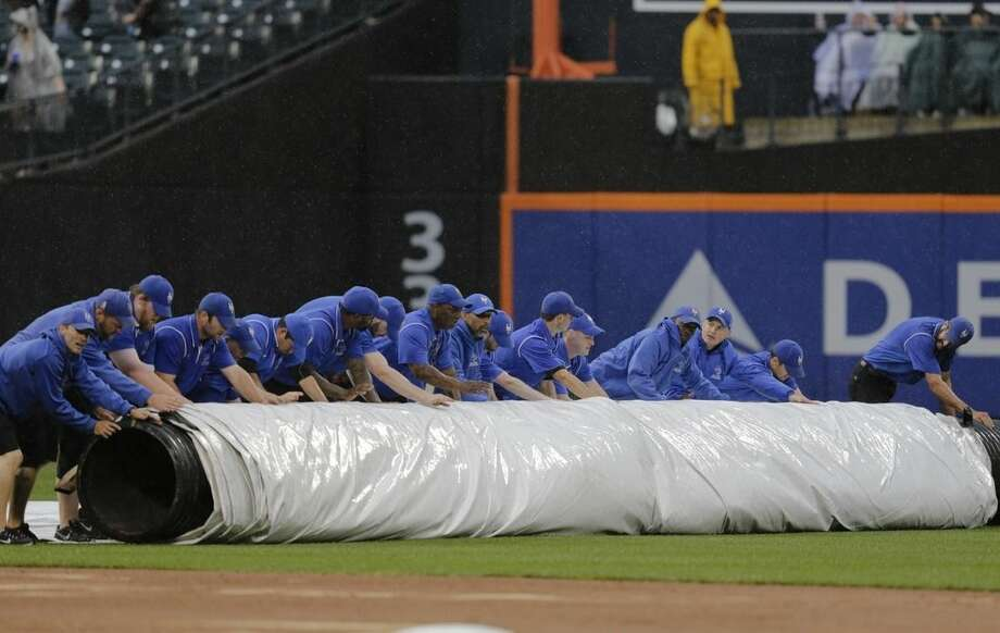 Grounds crew members cover the field during a rain delay during the seventh inning of a baseball game between the New York Mets and the Cincinnati Reds, Saturday, June 27, 2015, in New York. (AP Photo/Frank Franklin II)