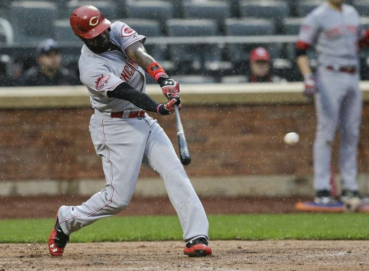 Cincinnati Reds' Brandon Phillips hits an hits an RBI-double in the rain during the fifth inning of a baseball game against the New York Mets, Saturday, June 27, 2015, in New York. (AP Photo/Frank Franklin II)