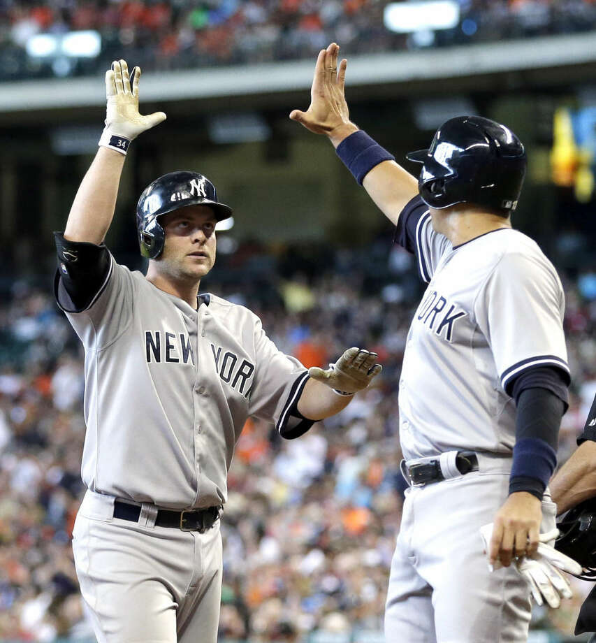 New York Yankees' Brian McCann, left, is congratulated by Alex Rodriguez, right, after hitting a grand slam against the Houston Astros during the first inning of a baseball game Saturday, June 27, 2015, in Houston. Chris Young, Brett Gardner, Rodriguez and McCann scored on the homer. (AP Photo/David J. Phillip)