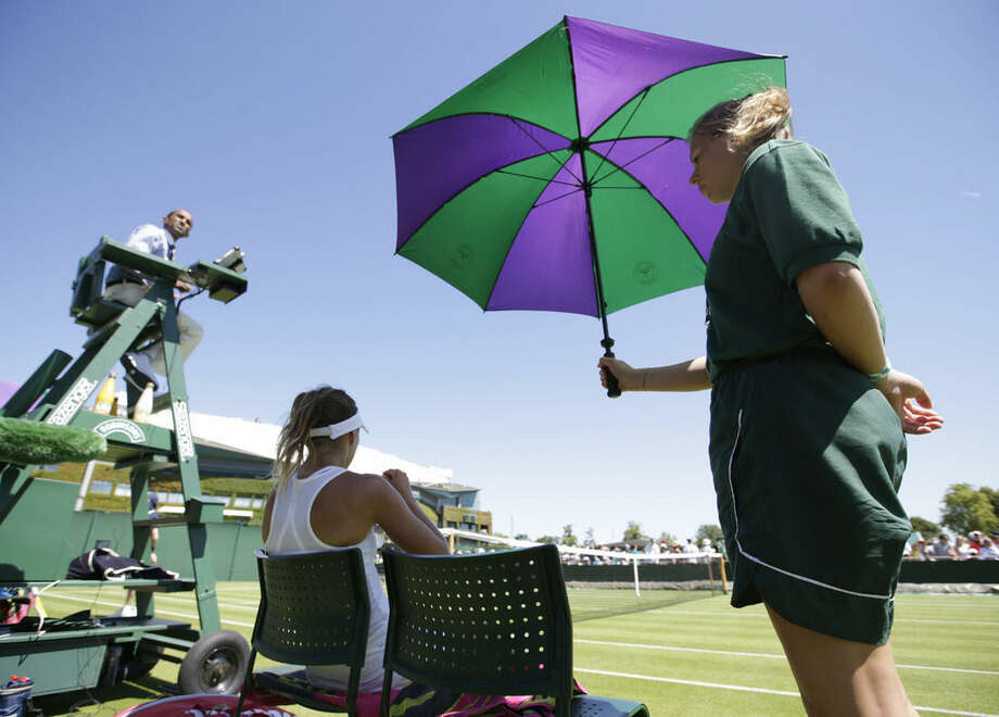 A ball girl shelters Magda Linette of Poland from the sun during a break in the women's singles first round match against Kurumi Nara of Japan at the All England Lawn Tennis Championships in Wimbledon, London, Tuesday June 30, 2015. (AP Photo/Alastair Grant)