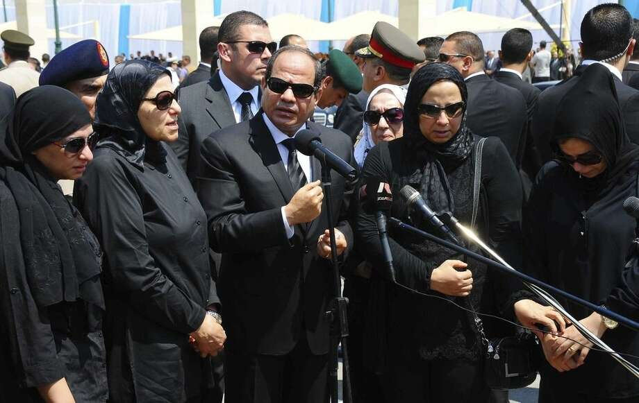In this picture taken Tuesday, June 30, 2015, provided by the office of the Egyptian Presidency, Egyptian president Abdel-Fattah el-Sissi, center, speaks at the funeral for Hisham Barakat, surrounded by his family members, the top judicial official in charge of overseeing the prosecution of thousands of Islamists, including former President Mohammed Morsi. The Egyptian president promised to speed up proceedings against extremists by amending laws and freeing up the judiciary, a day after the country's top prosecutor was killed in a car bombing. (Egyptian Presidency via AP)