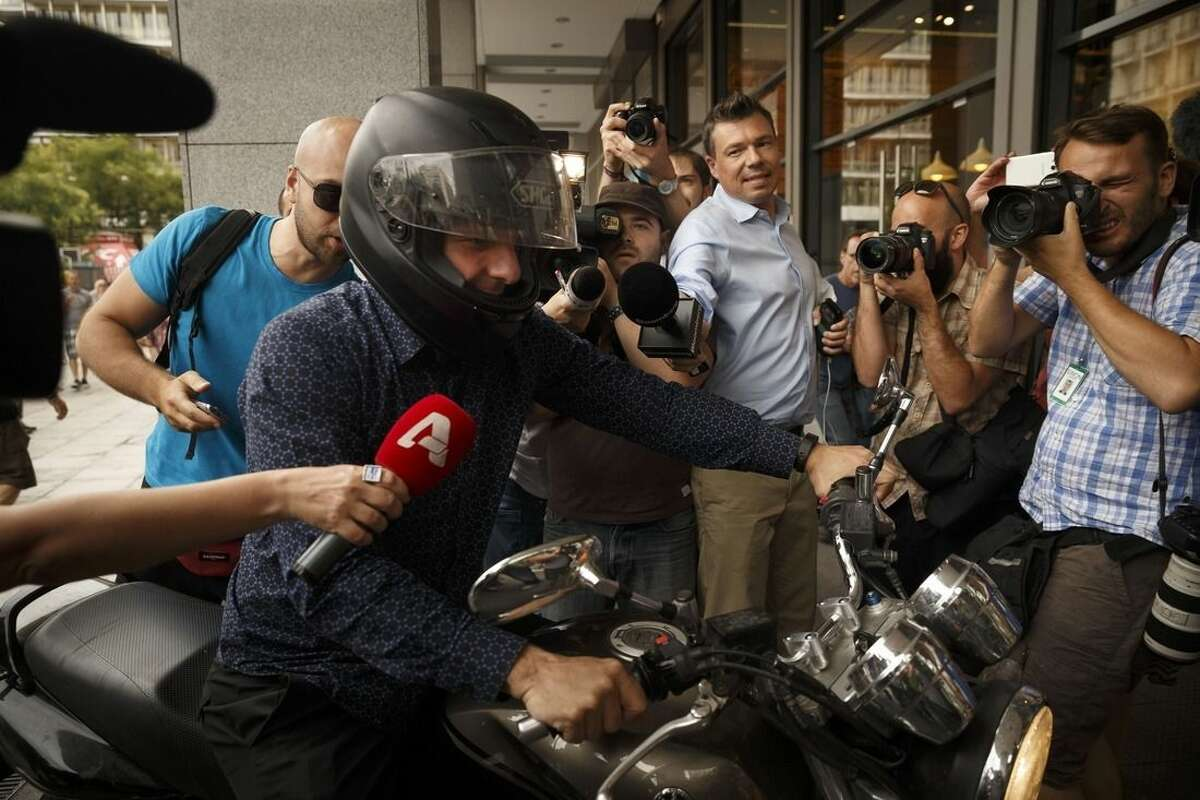 Greece's Finance Minister Yanis Varoufakis is surrounded by media as he leaves from his office in Athens, Tuesday, June 30, 2015. Greece is set to become the first developed nation to not pay its debts to the International Monetary Fund on time, as the country sinks deeper into a financial emergency that has forced it put a nationwide lockdown on money withdrawals. (AP Photo/Daniel Ochoa de Olza)