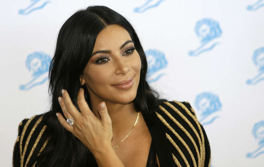 """FILE - In this June 24, 2015 file photo, American television personality Kim Kardashian poses for photographers as she attends the Cannes Lions 2015 in Cannes, southern France. The reality TV star is scheduled to speak and sign copies of her new coffee table book """"Selfish"""" during a Tuesday, June 30 night event hosted by the Commonwealth Club of California, which bills itself as the nation's oldest and largest public affairs forum.(AP Photo/Lionel Cironneau, File)"""
