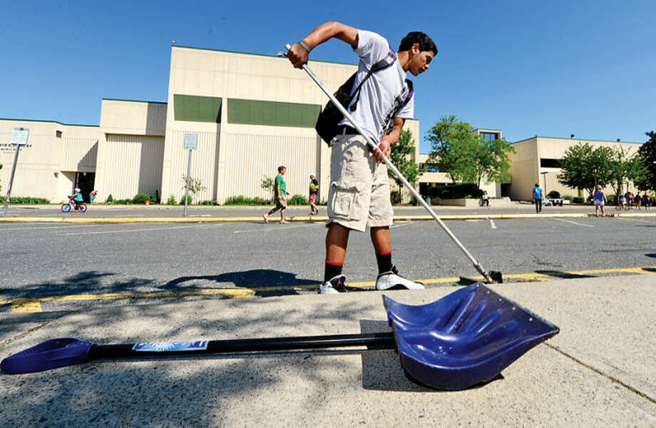 Hour photo / Erik Trautmann 11th grader Eric Cohens sweeps up the parking lot during the Norwalk High School 15th annual Campus Clean Up where over 200 students and teachers particpated in the planting of thousands of dollars worth of shrubs as well as the 15th White River Birch to honor a fallen veteran and alumni.