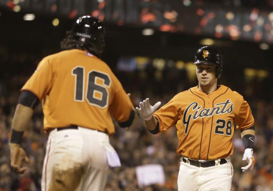 San Francisco Giants' Buster Posey, right, is congratulated by Angel Pagan (16) after Posey hit a two run home run off New York Mets' Carlos Torres in the eighth inning of a baseball game Friday, June 6, 2014, in San Francisco. (AP Photo/Ben Margot)