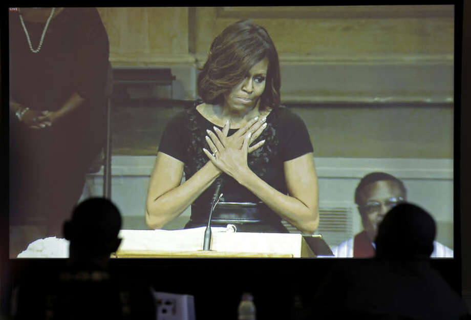 Media members watch on a screen as First lady Michelle Obama speaks during a memorial service for poet and author Maya Angelou at Wait Chapel. at Wake Forest University in Winston-Salem, N.C., Saturday, June 7, 2014. (AP Photo/Chuck Burton)