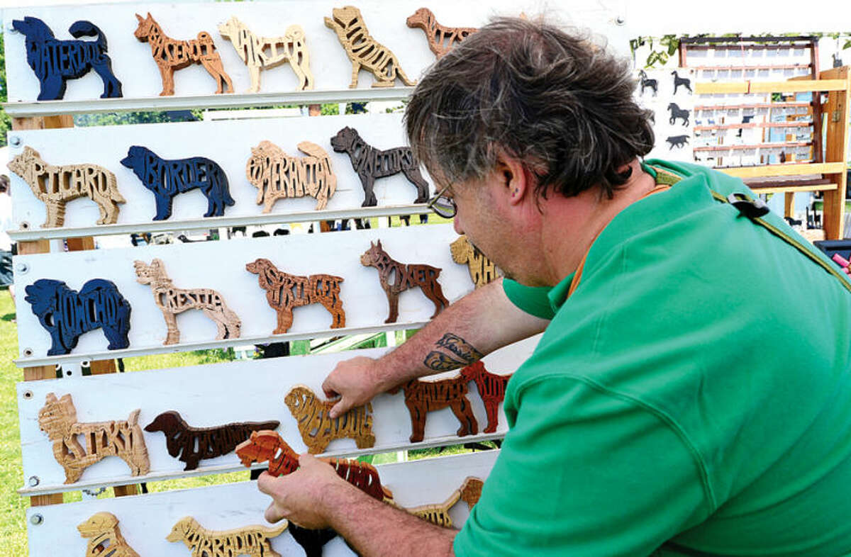 Hour photo / Erik Trautmann Ronald Raczowski puts out his canine puzzles during The Greenwich Kennel Club All-Breed Dog Show, Obedience & Rally Trial at Taylor Farm Saturday,
