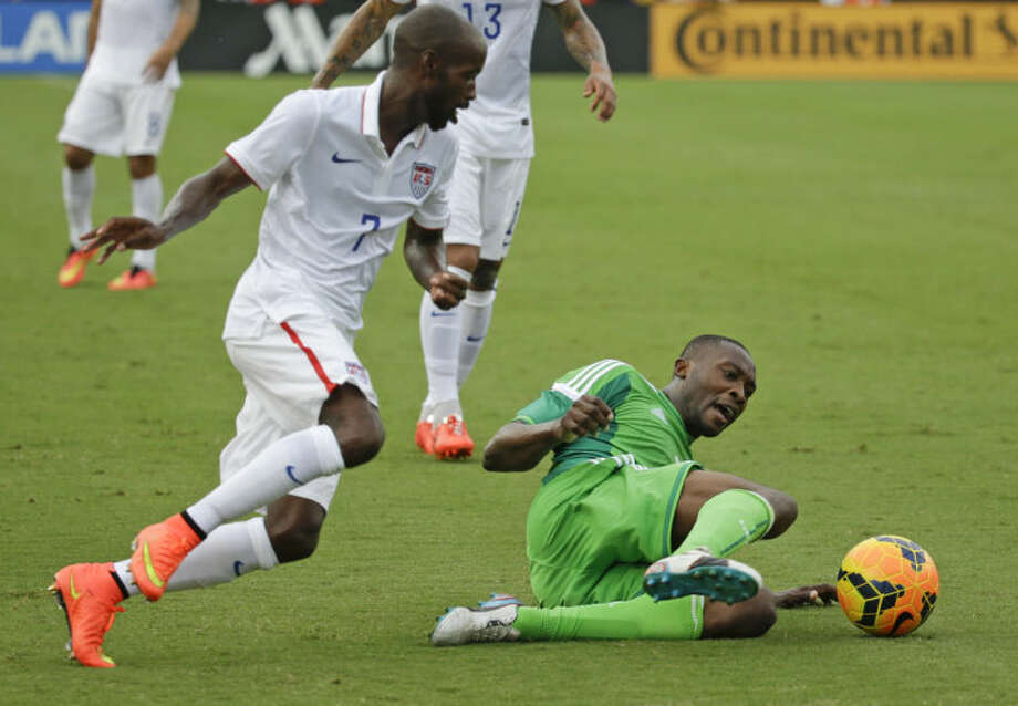 Nigeria's Shola Ameobi, right, tries to clear the ball away from United States's DaMarcus Beasley, left, during the first half of an international friendly soccer match in Jacksonville, Fla., Saturday, June 7, 2014. (AP Photo/John Raoux)