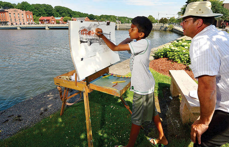 Hour photo / Erik Trautmann 10 year old Vihan Jayawardhane paints the Ruth Steinhaus Cohen Bridge in Westport while taking a drawing class with local artist Jim Chillington Tuesday.
