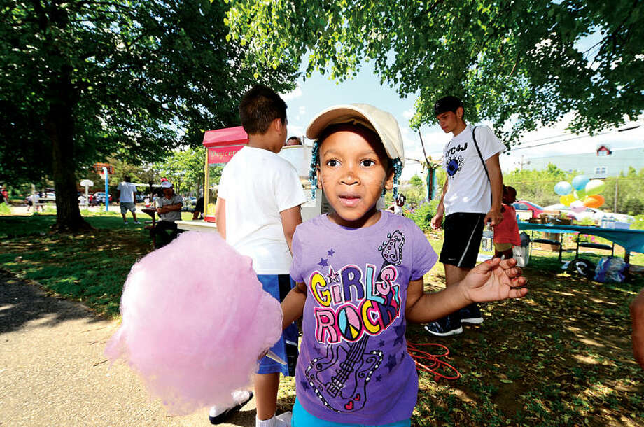 Hour photo / Erik Trautmann Miracle Caesar, 4, gets cooton candy during Rev. Ray Dancy's Youth Council for Justice Family Fun Day in Ryan Park Saturday.