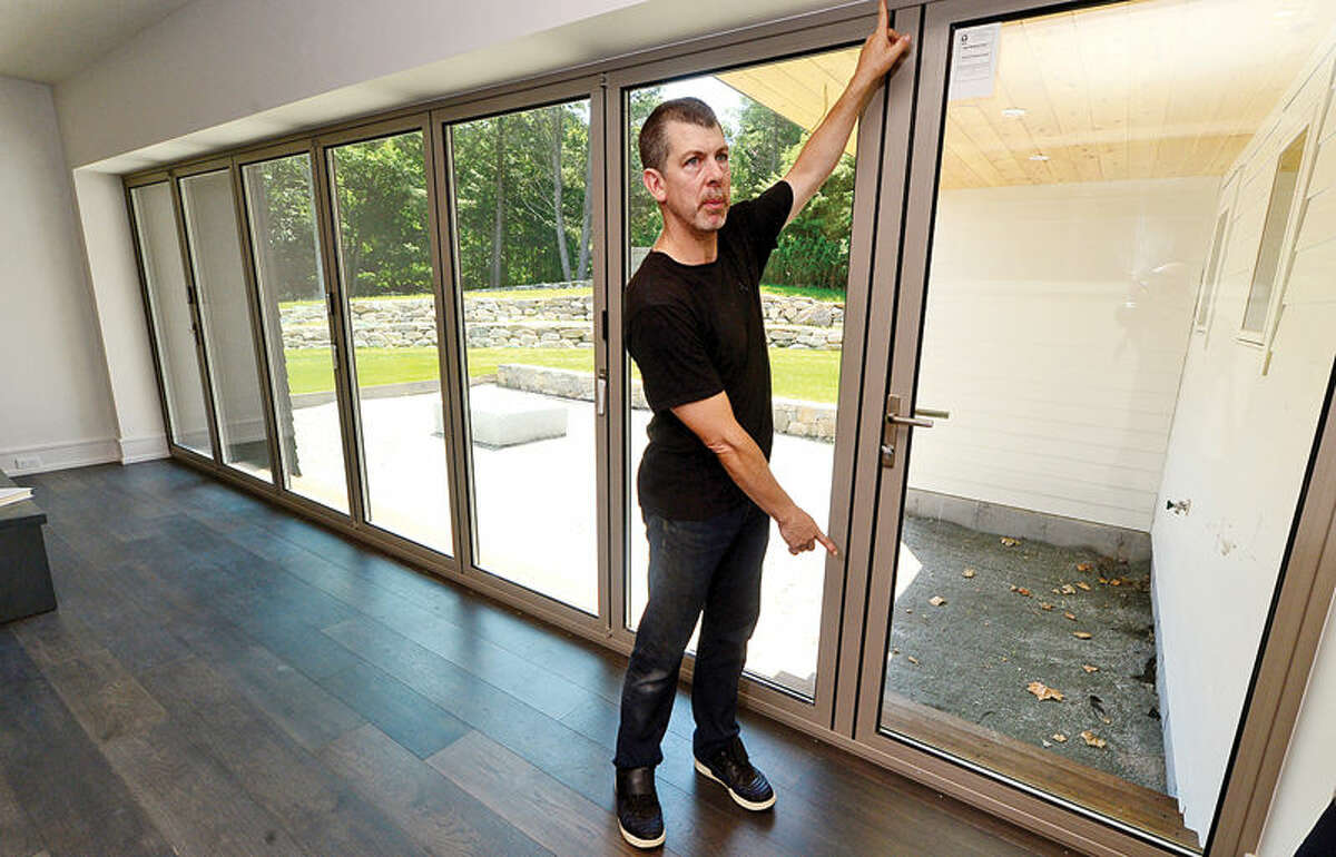 Hour photo / Erik Trautmann Doug McDonald, creator of The Pure House discusses the insulated windows at a newly constucted Pure House is for sale at 100 Coleytown Road in Westport. The Pure House purpose is to maximize comfort levels while minimizing or eliminating its energy footprint as well as using natural materials that don't include any of the known toxins on the Google Red List.