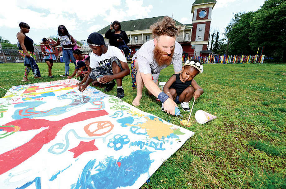 Hour photo / Erik Trautmann New Haven artist Damian Paglia helps 2 year old Haley patterson paint a banner during Rev. Ray Dancy's Youth Council for Justice Family Fun Day in Ryan Park Saturday.
