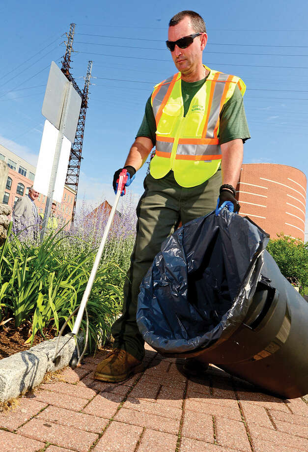 Hour photo / Erik Trautmann Norwalk Public Works employee Neil Dennehy, Clean Street Ambassador, helps with the Mayor's Clean Street Intiative Tuesday in front of IMAX/Seaport Dock on North Water as Norwalk Mayor Harry Rilling held a press conference to discuss the possible acquisition of a Madvac street vacuum and the addition of the Clean Street Ambassador to help with his Clean Street Intitiative.