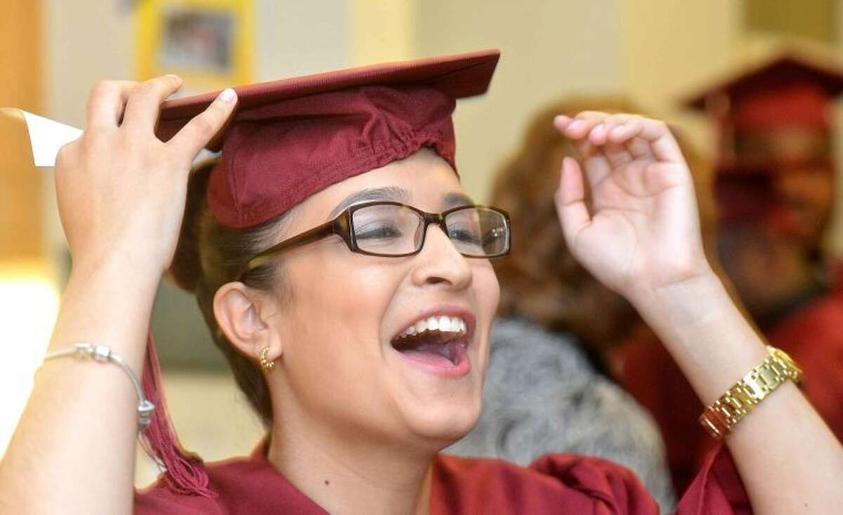 Hour Photo/Alex von Kleydorff Yuliana Herrera shares a laugh with other graduates at the Norwalk Adult Ed. Graduation ceremony