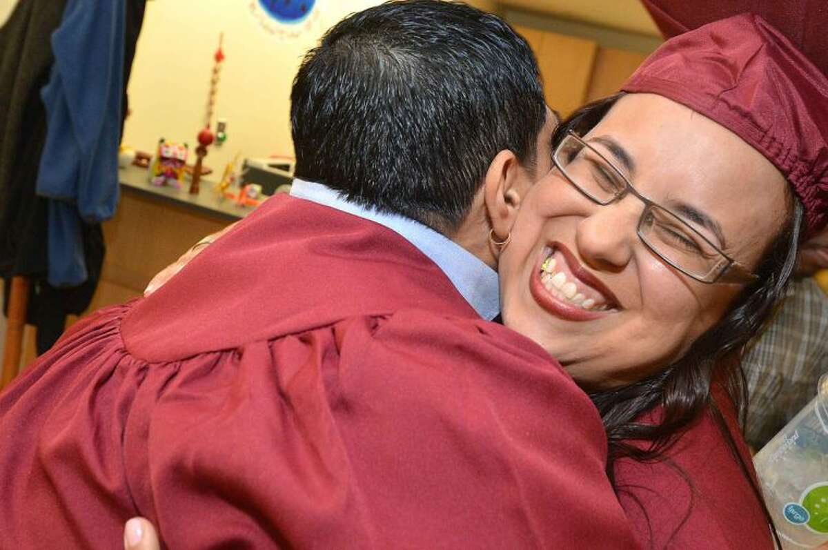 Hour Photo/Alex von Kleydorff Lissette Grijalva gets a big hug from a fellow graduate at Norwalk Adult Ed. Graduation. She is graduating along with her daughter Evelyn
