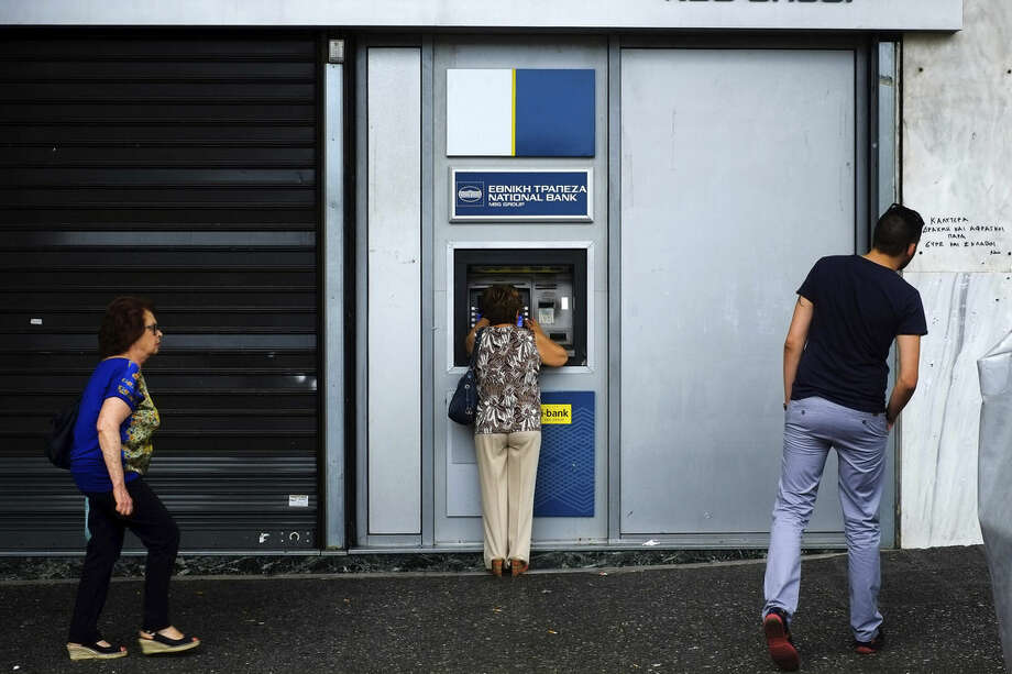 A woman uses an ATM outside of a closed bank five days before the upcoming referendum, in central Athens, on Tuesday, June 30, 2015. Greek Finance Minister Yanis Varoufakis confirmed that the country will not make its payment due later to the International Monetary Fund. Capital controls began Monday and will last at least a week, an attempt to keep the banks from collapsing in the face of a nationwide bank run. (AP Photo/Petros Karadjias)