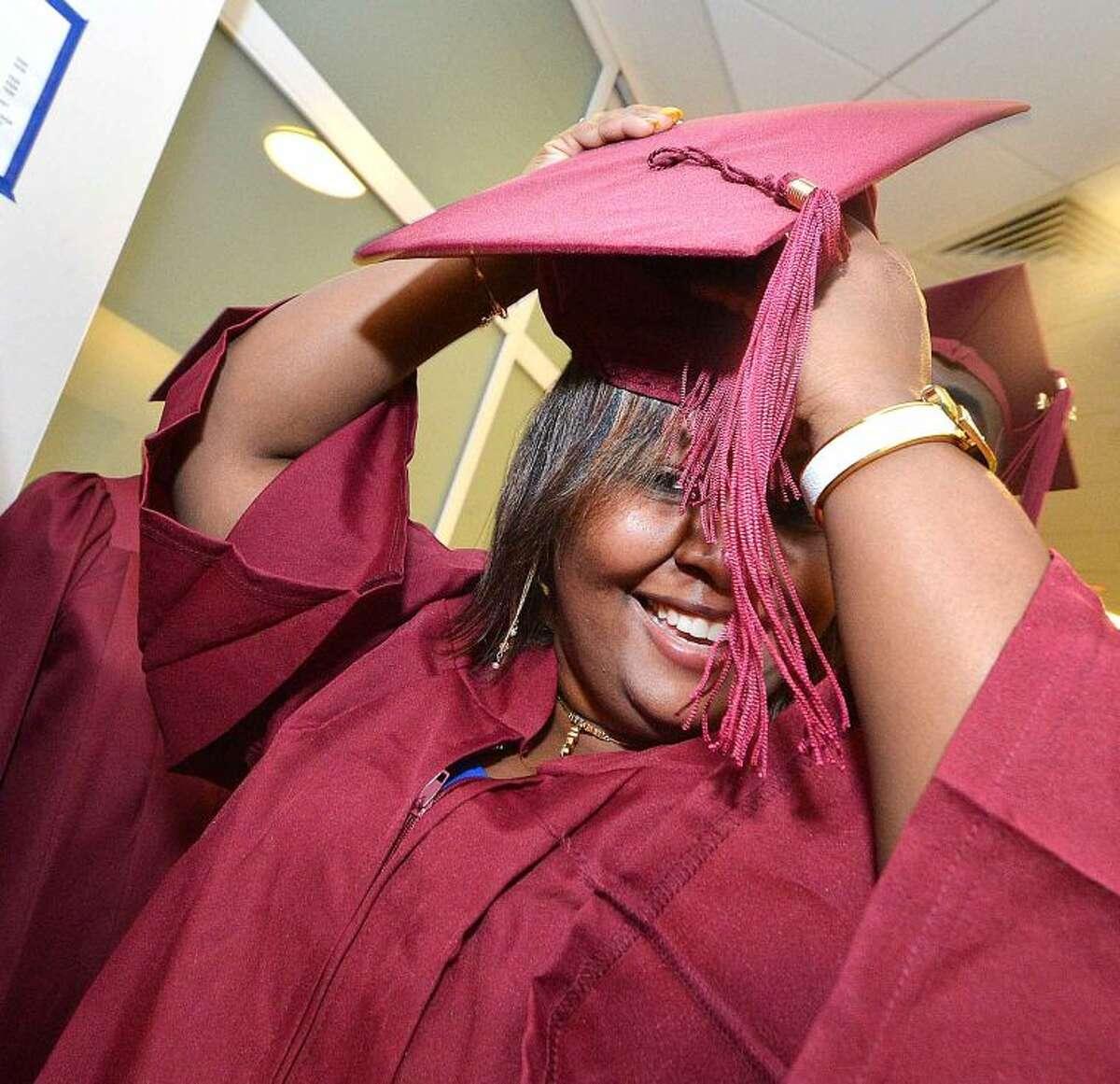 Hour Photo/Alex von Kleydorff Gina Michelle gets her cap together at Graduation for Adult Ed.