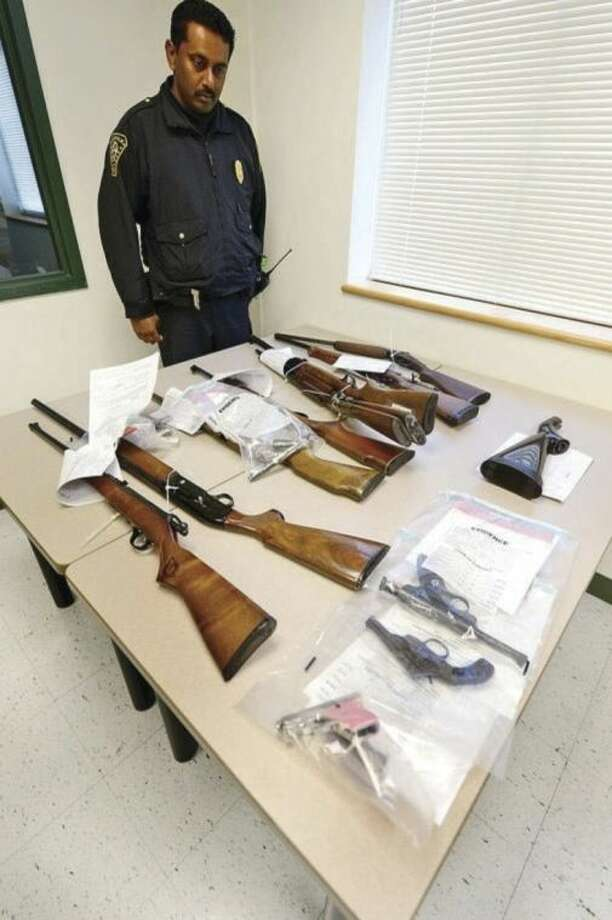 Hour file photo / Erik TrautmannIn this Feb. 2, 2013 file photo, Lt. Praveen John looks over guns turned in during the The Norwalk Police Department's first ever Gun Buy Back program. This year's program will be held Saturday, June 14 from 9 a.m. to 1 p.m.