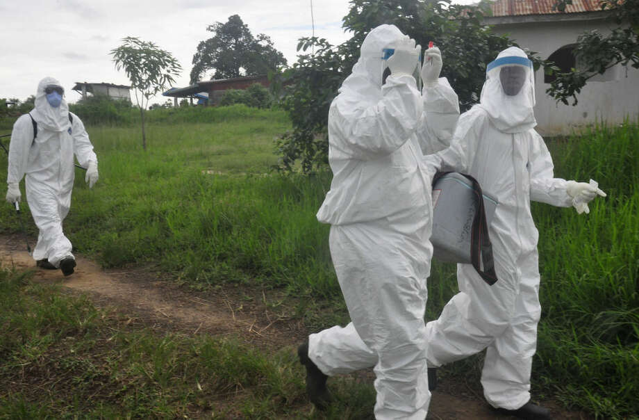 Health workers leave after they took a blood specimen from a child to test for the Ebola virus in a area were a 17-year old boy died from the virus on the outskirts of Monrovia, Liberia, Tuesday, June 30, 2015. Liberian authorities on Tuesday quarantined an area where the corpse was found, sparking fears this West African country could face another outbreak of the disease nearly two months after being declared Ebola-free. (AP Photo/ Abbas Dulleh)