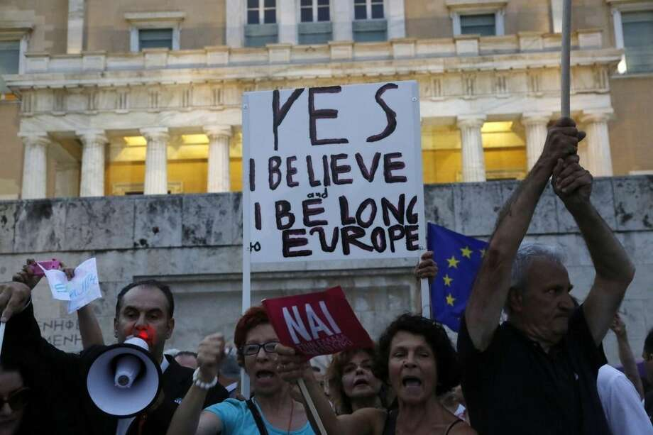 Demonstrators shout slogans during a rally organized by supporters of the YES vote for the upcoming referendum in front of the Greek Parliament in Athens, Tuesday, June 30, 2015 Greece's European creditors were assessing a last-minute proposal Athens made for a new two-year rescue deal, submitted just hours before the country's international bailout program expires and it loses access to billions of euros in funds. (AP Photo/Petros Karadjias)