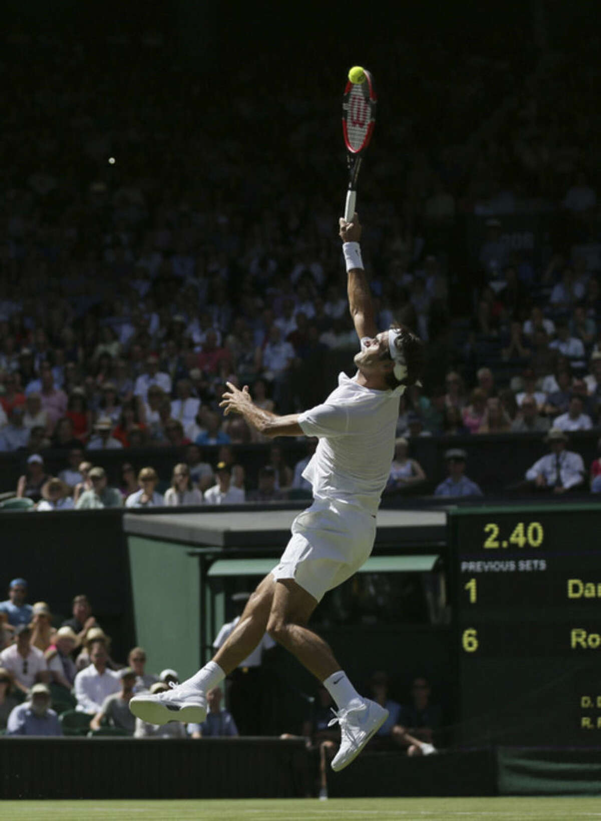 Roger Federer of Switzerland smashes a ball to Damir Dzumhur of Bosnia during the singles first round match at the All England Lawn Tennis Championships in Wimbledon, London, Tuesday June 30, 2015. (AP Photo/Tim Ireland)