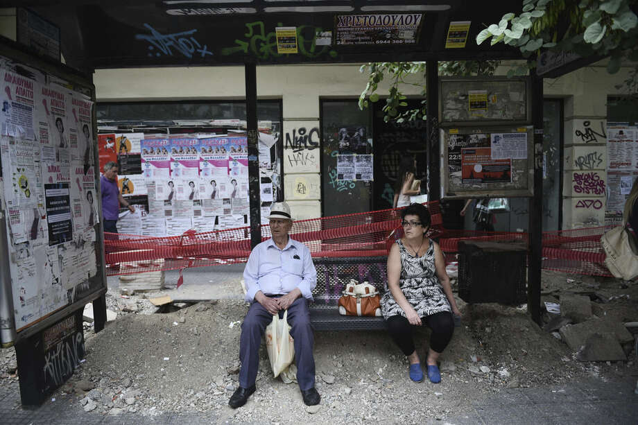 An elderly man and a woman wait at a bus stop as the sidewalk is under construction in the northern Greek port city of Thessaloniki, Tuesday, June 30, 2015. Greek Finance Minister Yanis Varoufakis confirmed that the country will not make its payment due later to the International Monetary Fund. Capital controls began Monday and will last at least a week, an attempt to keep the banks from collapsing in the face of a nationwide bank run. (AP Photo/Giannis Papanikos)