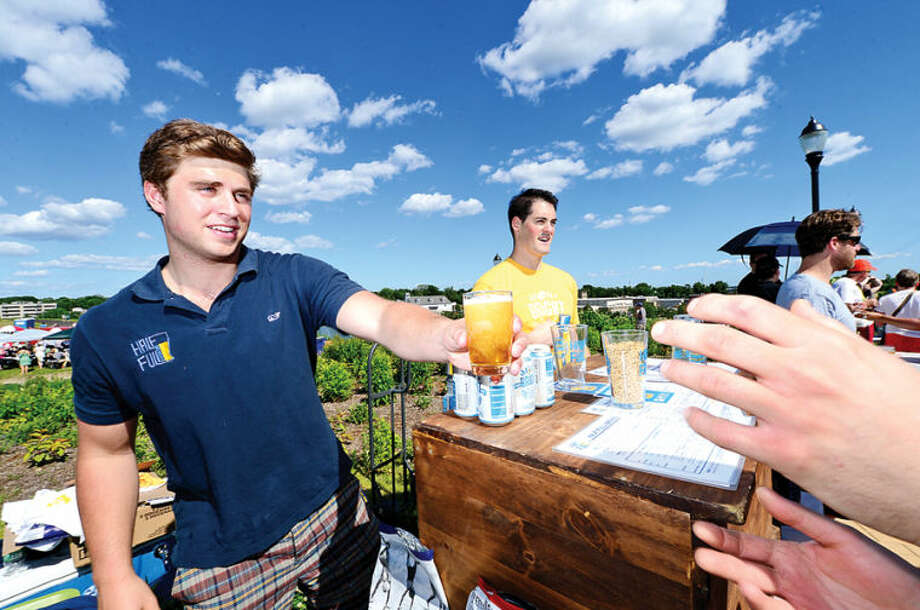 Hour photo / Erik Trautmann Nearly 500 people enjoy 18 different craft breweries including Half Full Brewery from Stamford tended by Chief Beer Entertainer Ben Hoeff and asistant Stuart Lovejoy during Ninety9 Bottles' first ever Craft Beer Festival at Oyster Shell Park Saturday.