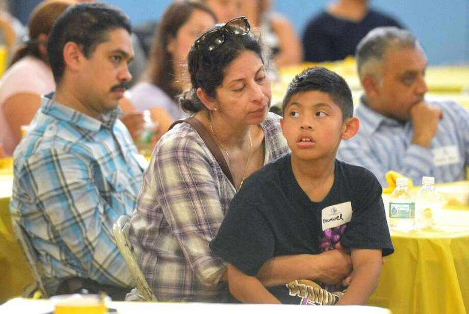 Hour Photo/Alex von Kleydorff Luz Hernadez listens with her son 8yr old Emanuel Canahui during the presentation of the new literacy program at Brookside School