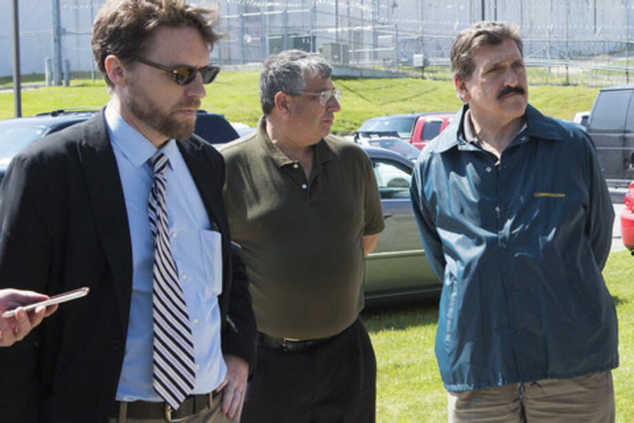 In a Saturday, June 6, 2015 photo, Clinton Correctional Superintendent Steven Racette, center, listens to Gov. Andrew Cuomo speak during a press conference in Dannemora, N.Y. Officials said Tuesday, June 30, 2015, that Racette and his deputy in charge of security are among 12 more staff who have been put on administrative leave during the investigation into David Sweat and Richard Matt's escape from the maxiumum-security Clinton Correctional Facility. (Gabe Dickens/The Press-Republican via AP)