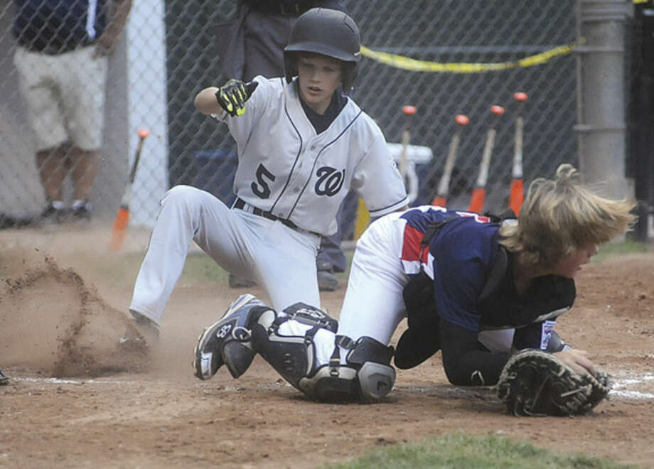 Hour photo/Matthew VinciWilton's Everett Andersen slides safely into home plate past Stamford catcher Ben Nash.