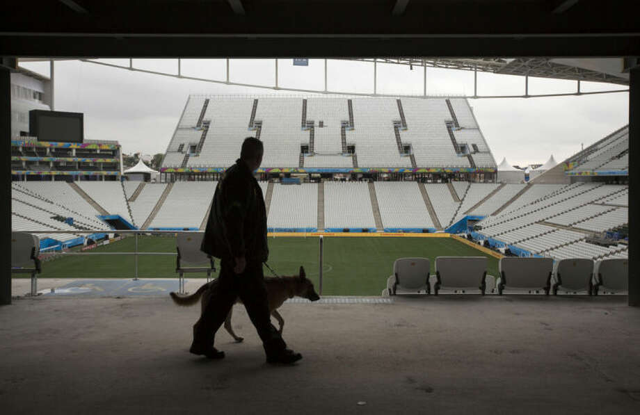 A federal police officer walks with a sniffer dog as they search for explosives during a security check one day before the opening World Cup soccer match in Itaquerao Stadium in Sao Paulo, Brazil, Wednesday, June 11, 2014. If Brazil wins the opening game, the fact that Itaquerao stadium isn't even fully finished yet will quickly be forgotten. (AP Photo/Felipe Dana)
