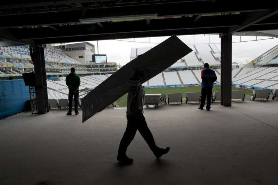 A worker carries cardboard inside Arena Corinthians stadium in Sao Paulo, Brazil, Wednesday, June 11, 2014. The World Cup soccer tournament starts Thursday. (AP Photo/Rodrigo Abd)