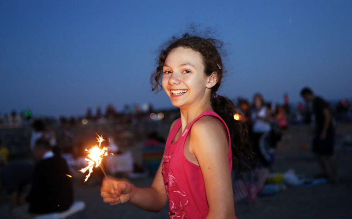 Emily Ruhnke, 10, plays with a sparkler before Norwalk's annual firework display at Calf Pasture Beach Saturday evening. Hour Photo / Danielle Calloway