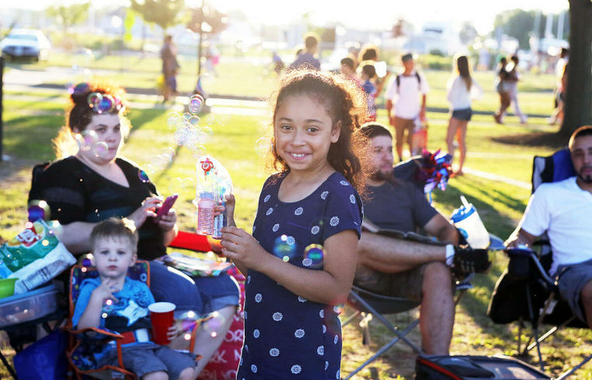 Avani Lopez , 9, uses a bubble maker before Norwalk's annual firework display at Calf Pasture Beach Saturday evening. Hour Photo / Danielle Calloway
